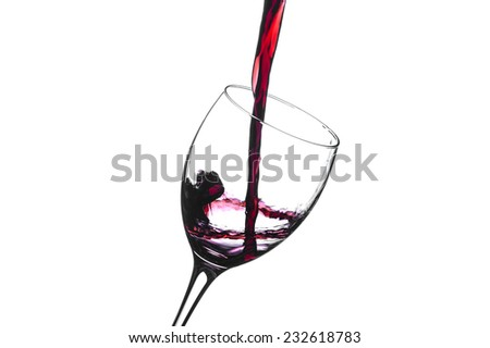 Pouring red wine into a  moving wine glass isolated on a white background