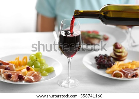 Pouring red wine into glass from bottle in restaurant