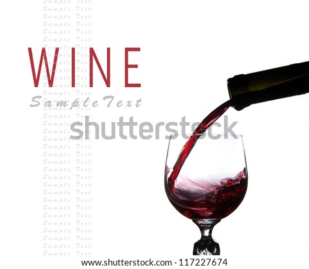 Pouring red wine into glass isolated on white background
