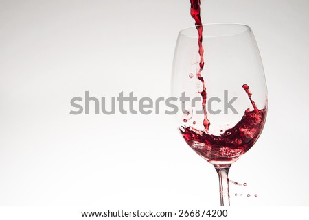 Pouring red wine into glass on white background - stock photo