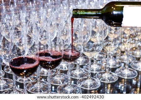 Pouring red wine into many glass. waiters poured into glasses of wine for night event party. Selective focus  - stock photo