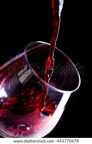 Pouring red wine into the glass - stock photo