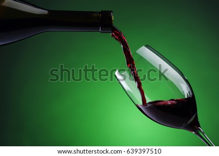 Pouring red wine into wine glass on green background. Closeup