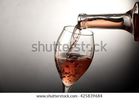 Pouring rose wine from bottle into the wineglass - stock photo