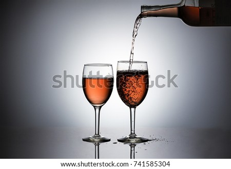 Pouring rose' wine in a glass.