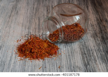 Pouring saffron in glass bottle on old wooden table. - stock photo