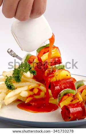 Pouring sauce on grilled meat and vegetable kebabs on the white plate - stock photo