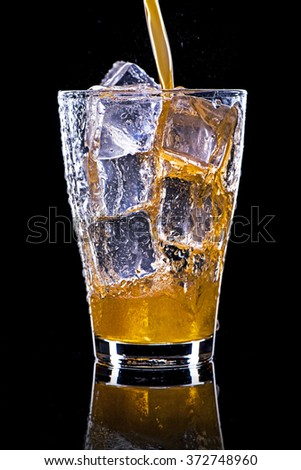 Pouring soft drink in a glass with ice on a black background