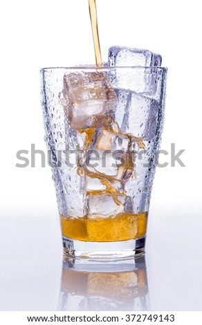 Pouring soft drink in a glass with ice on an isolated white background