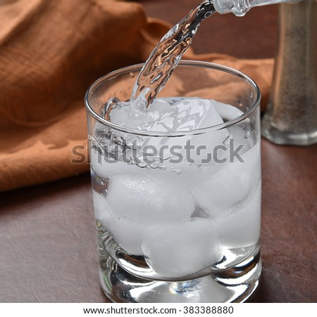 Pouring sparkling water into a glass - stock photo