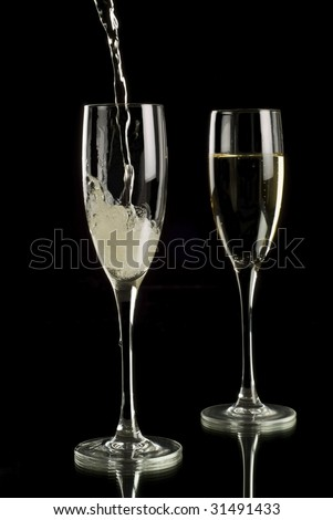 Pouring sparkling wine into champagne flutes on a black background with reflection in a mirror
