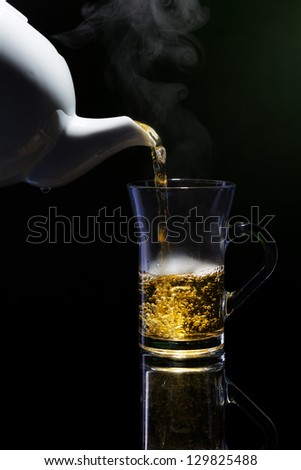 pouring steaming hot fresh healthy green tea from tea-can - stock photo
