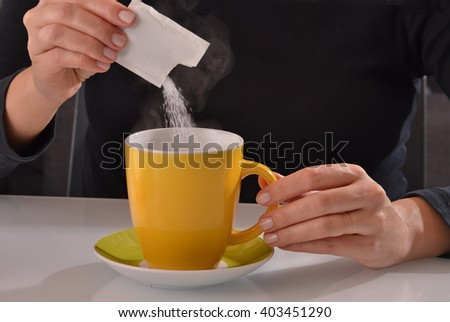 Pouring sugar bag on coffee cup. - stock photo