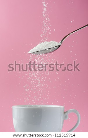 Pouring sugar in coffee cup - stock photo