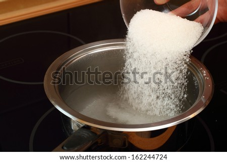 Pouring sugar into saucepan with boiling water. Candied Orange Zest Cooking. Series. - stock photo