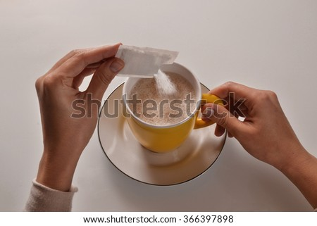 Pouring sugar on coffee cup. - stock photo
