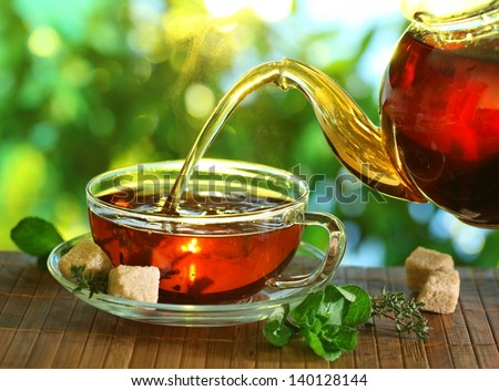 Pouring tea from a teapot into a cup on a blurred background of nature. - stock photo