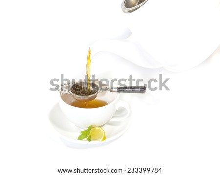 Pouring tea into a cup with lemon and mint