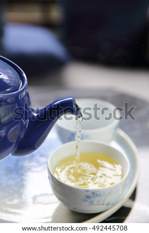 pouring tea into cup of tea in close up Chinese and Japan drink