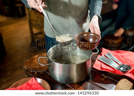 pouring the soup - stock photo