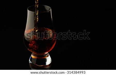 Pouring up a glass of whisky isolated over black background