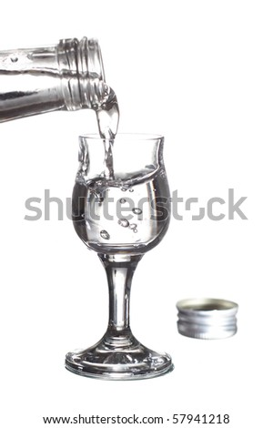 pouring vodka from a bottle into a glass