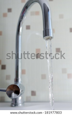 Pouring water from a tap in a bathroom