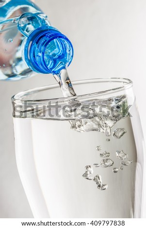 Pouring water from bottle into glass closeup - stock photo