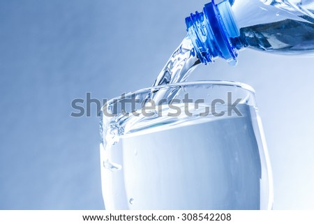 Pouring water from bottle into glass in blue toning - stock photo