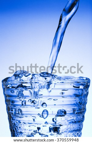 Pouring water from bottle into glass on blue background - stock photo