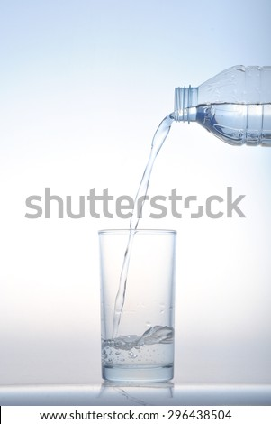Pouring water from bottle into glass on blue background, water glass, Water pour into glass
