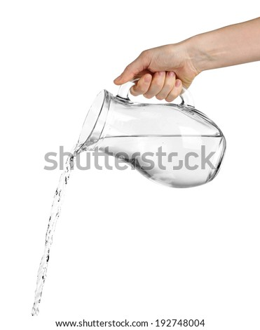 Pouring water from glass pitcher, isolated on white - stock photo