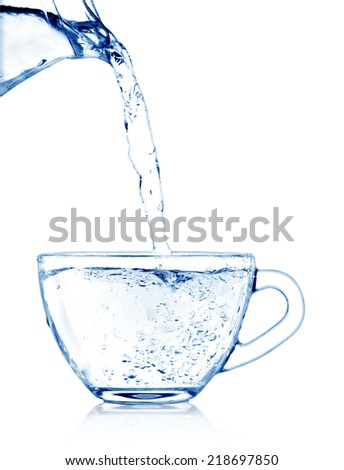 Pouring water from pitcher into a glass mug - stock photo