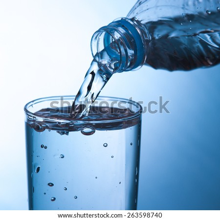 pouring water in glass - stock photo