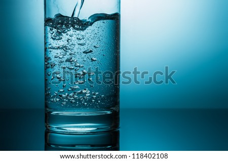 pouring water in glass closeup in blue light - stock photo