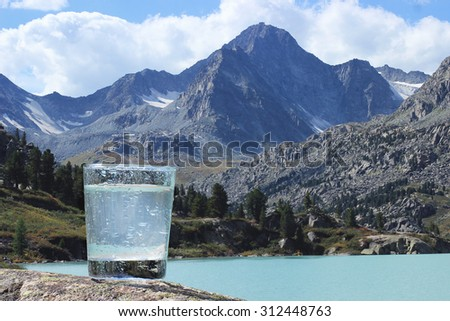Pouring Water Into Glass Against Nature Stock Photo