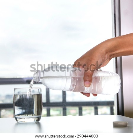 Pouring water into a glass in the house