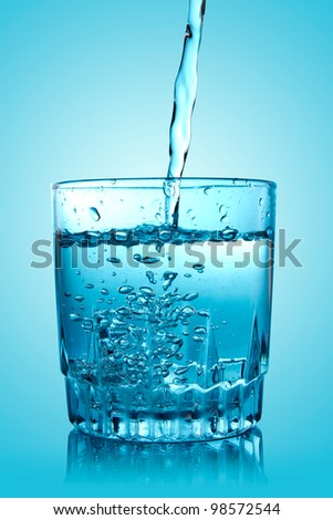 pouring water into a glass with reflection on blue background