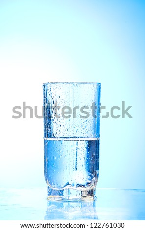 Pouring water into glass  and Glass of water on a blue background - stock photo