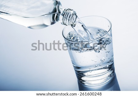 pouring water into glass from a bottle, on blue background - stock photo