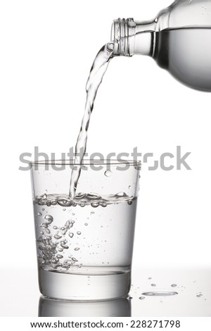 pouring water into glass from a bottle, on white background - stock photo