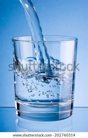 Pouring water into glass on a blue background - stock photo