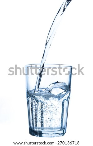 Pouring water into glass on white background - stock photo