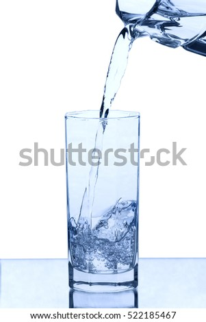 Pouring water into the glass on white background
