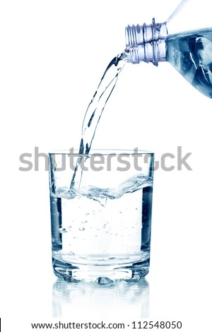 pouring water on a glass on white background - stock photo