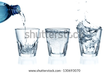 Pouring water on a glass on white background. Ice cubes splashing into glass of water - stock photo