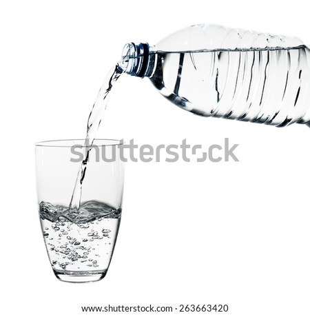 Pouring water on glass isolated on white - stock photo