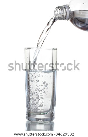 Pouring water on glass isolated on white