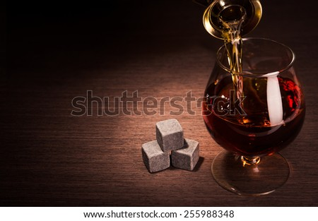 Pouring whiskey beverage in glass with stone. Alcohol background. - stock photo