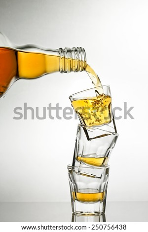 pouring whiskey into shot glasses - stock photo